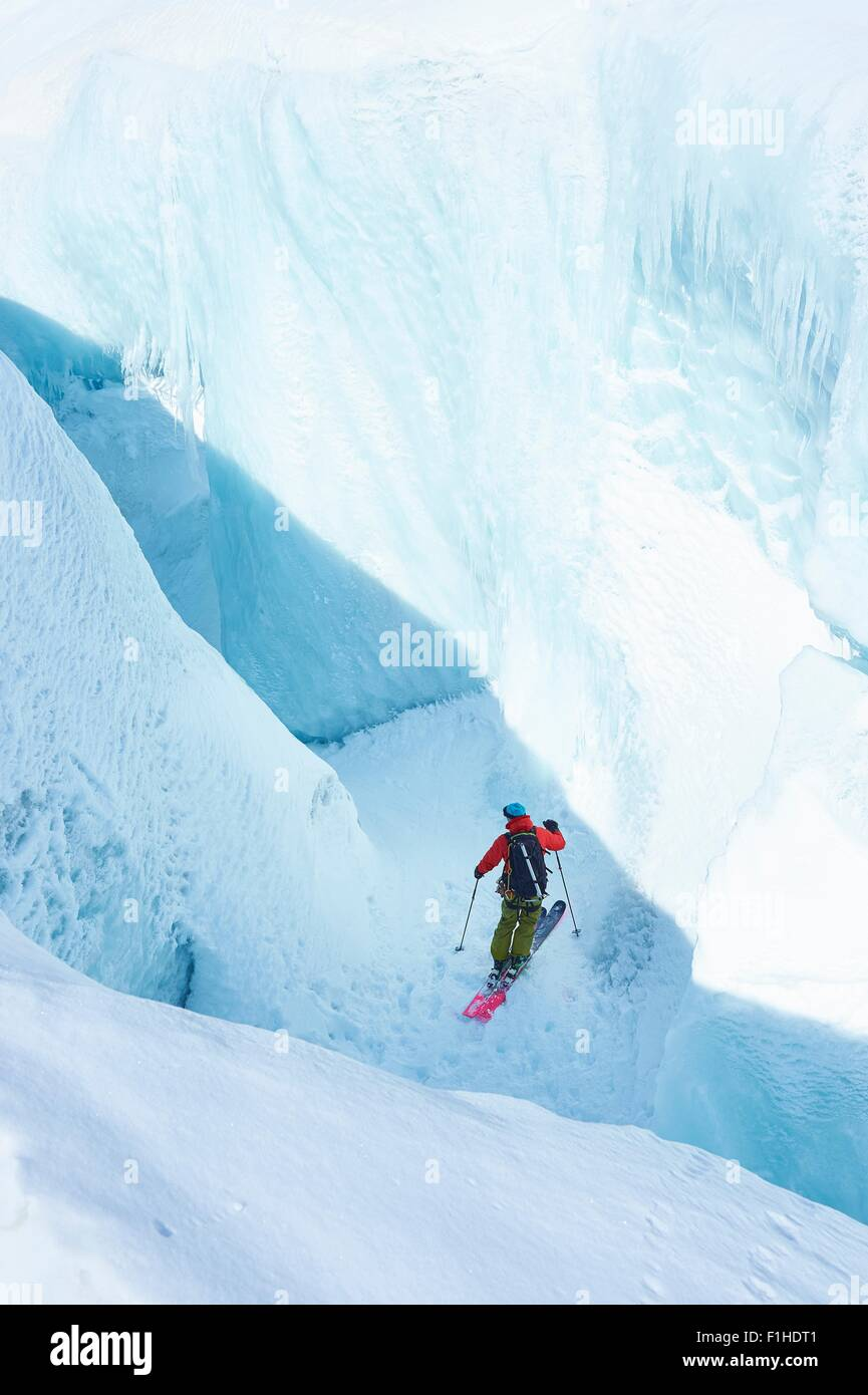 Male skier skiing down ravine on Mont Blanc massif, Graian Alps, France - Stock Image