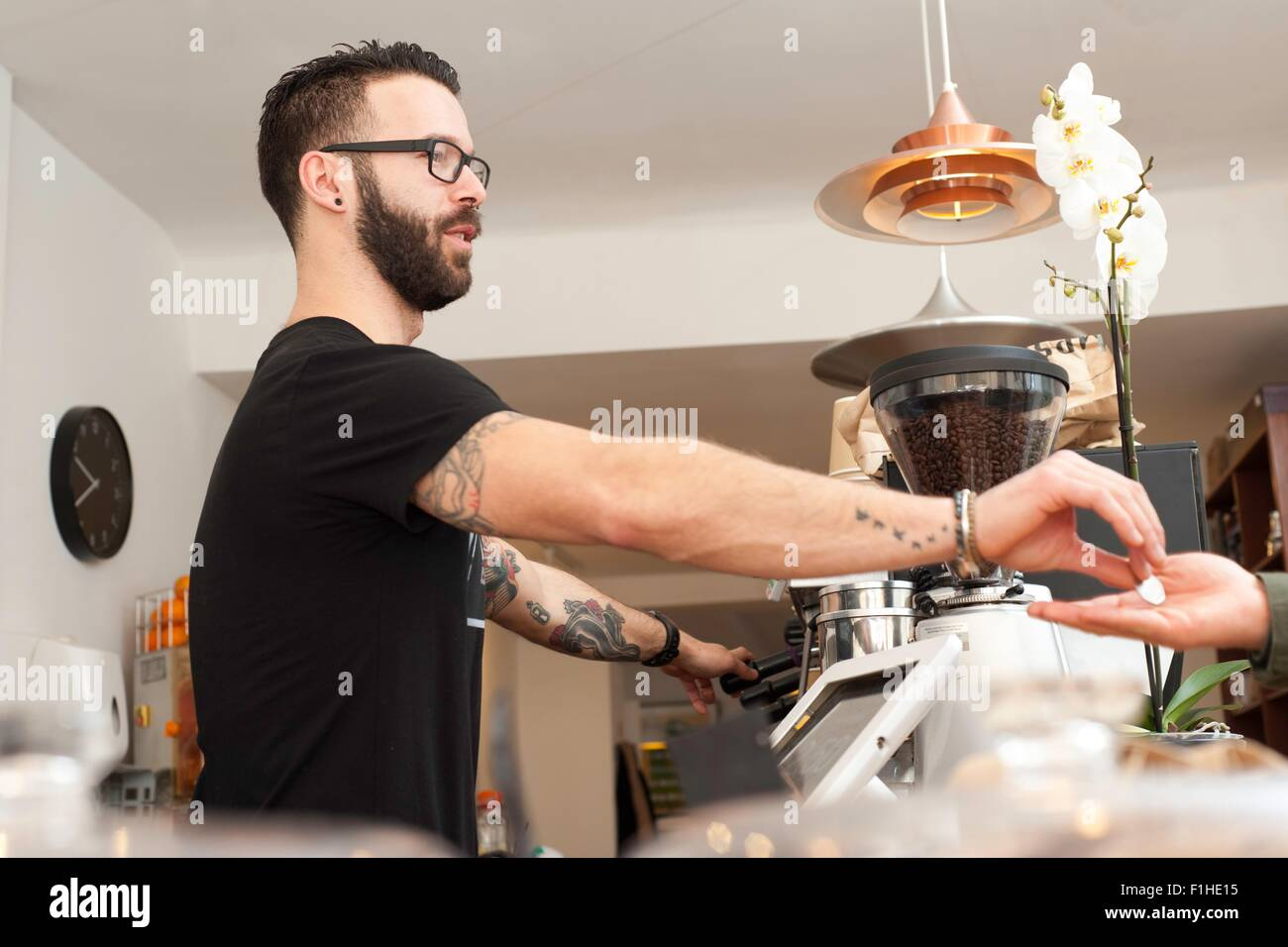 Cafe waiter handing coins to customer from behind counter - Stock Image