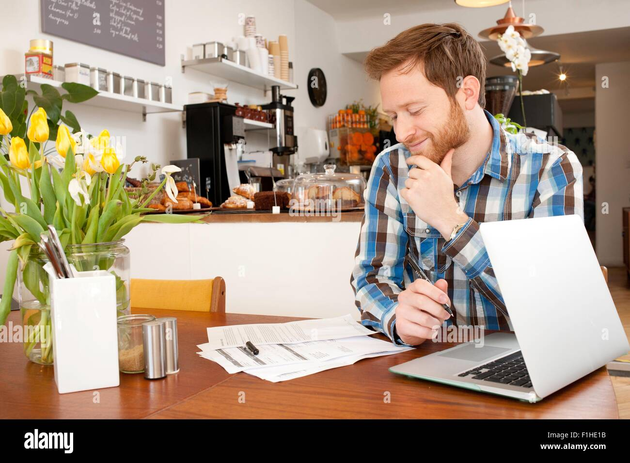 Male customer filling in application form in cafe - Stock Image