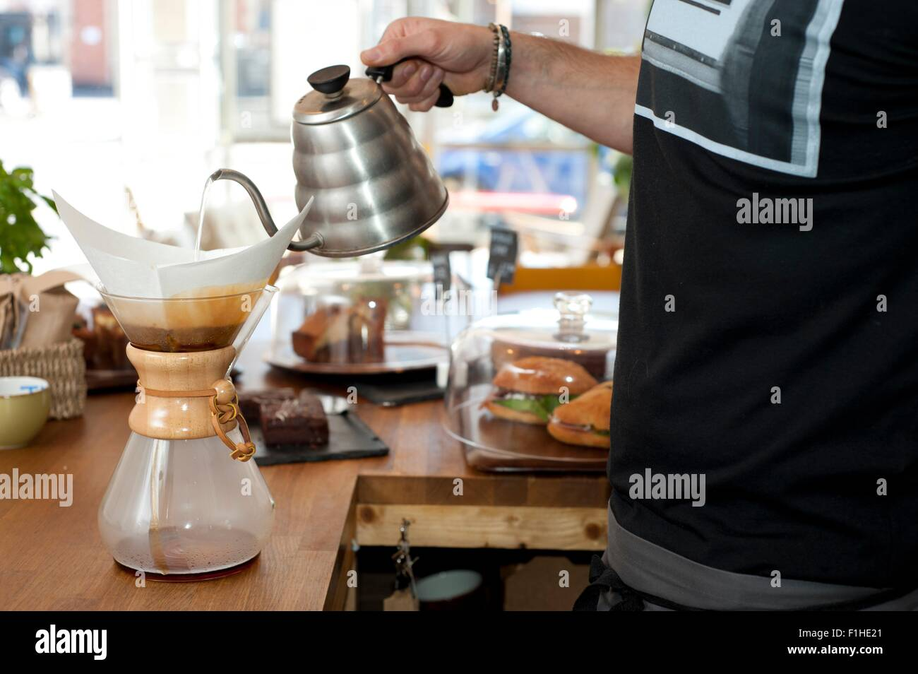 Hand of cafe waiter pouring boiling water into filter coffee pot - Stock Image