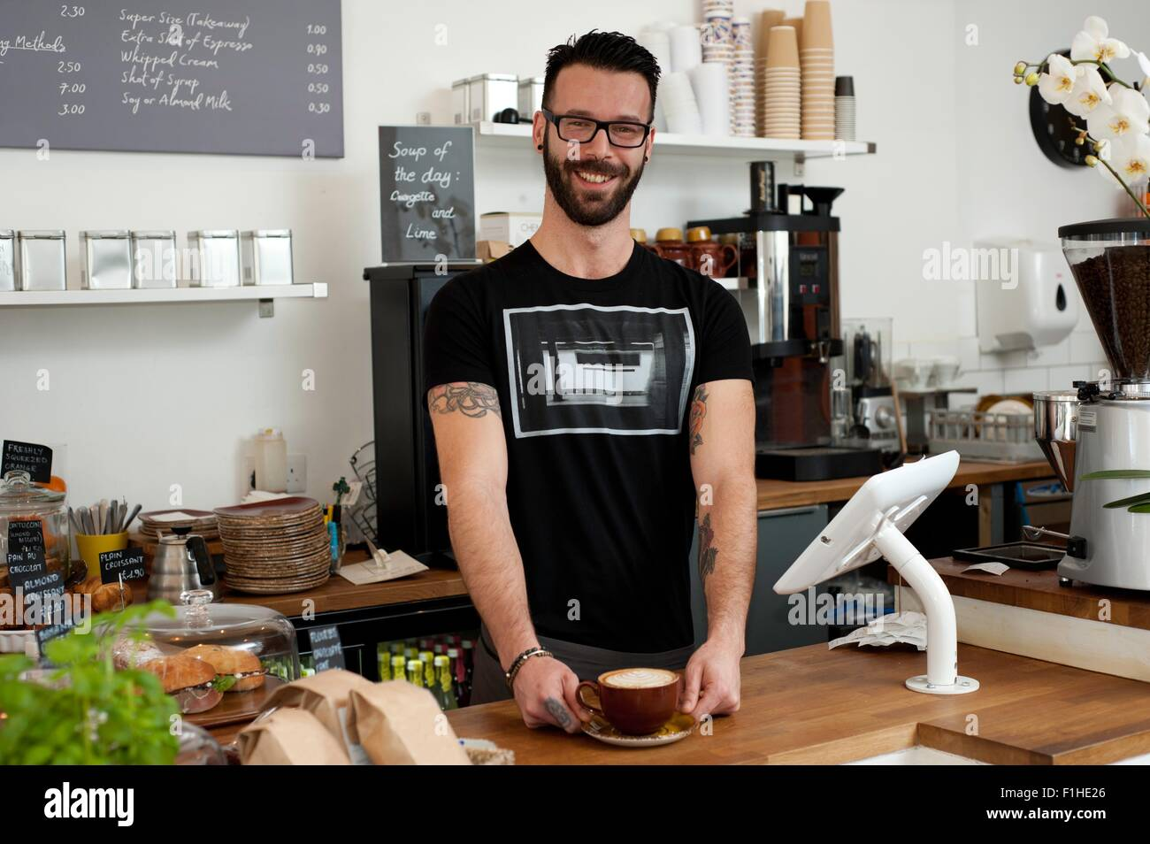 Portrait of cafe waiter serving coffee from counter - Stock Image