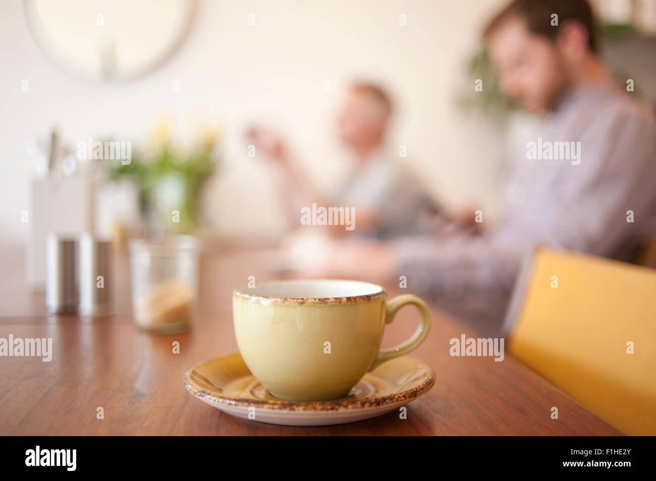 Cup on table and people in background in a cafe - Stock Image