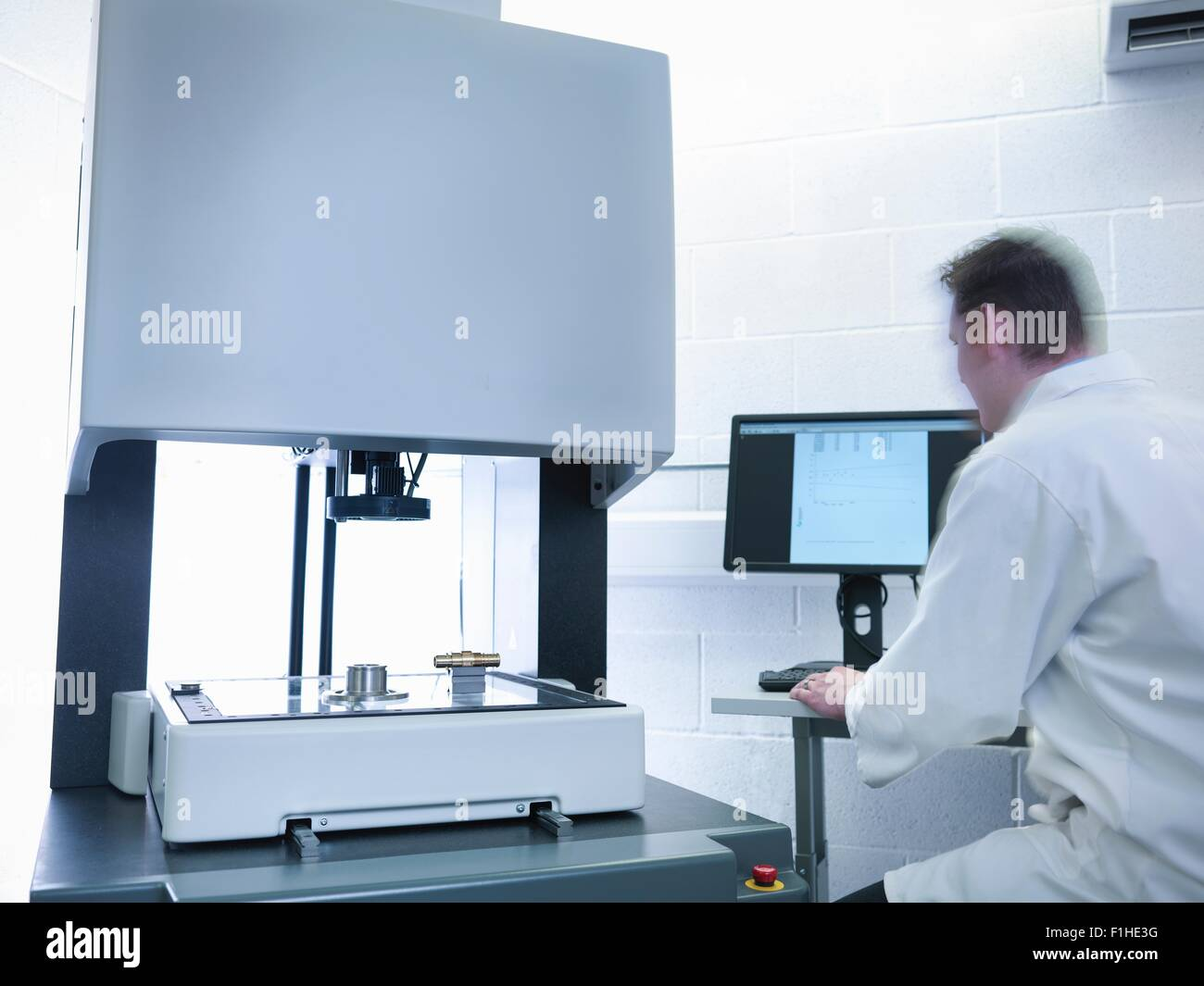 Engineer measuring parts in quality control room - Stock Image