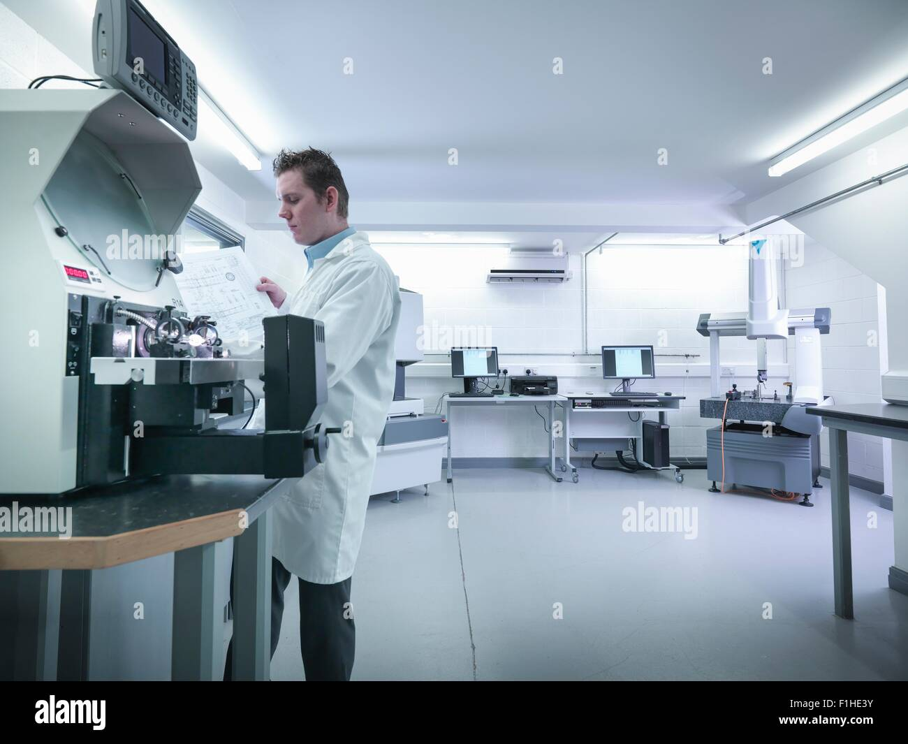 Quality control engineer measuring parts in quality control room - Stock Image