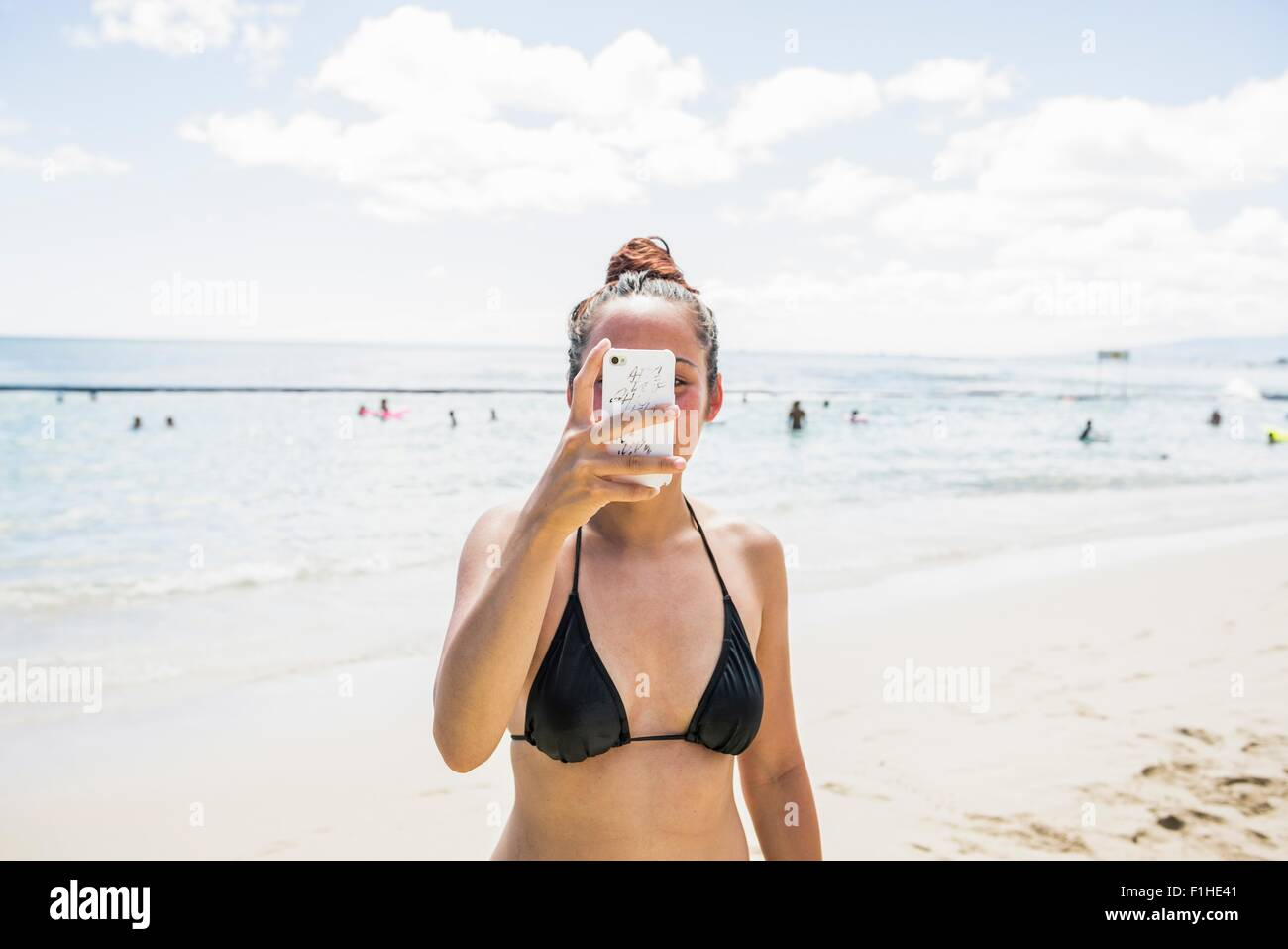 Young woman wearing bikini top taking smartphone selfie on Waikiki Beach, Hawaii, USA - Stock Image