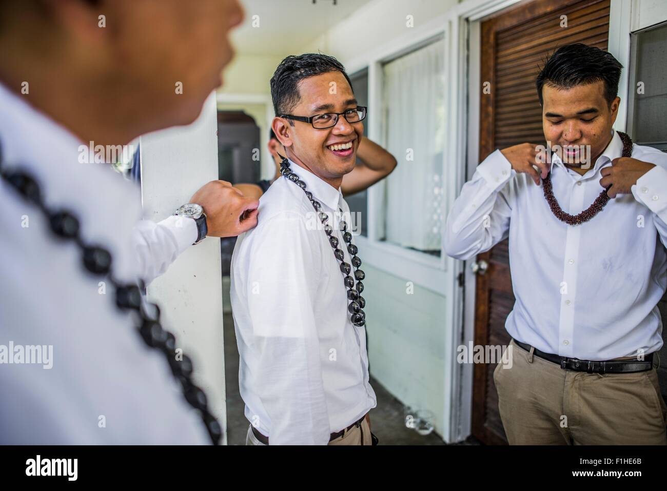 Three young men preparing for Hawaiian wedding wearing kukui nut beads, Kaaawa, Oahu, Hawaii, USA - Stock Image