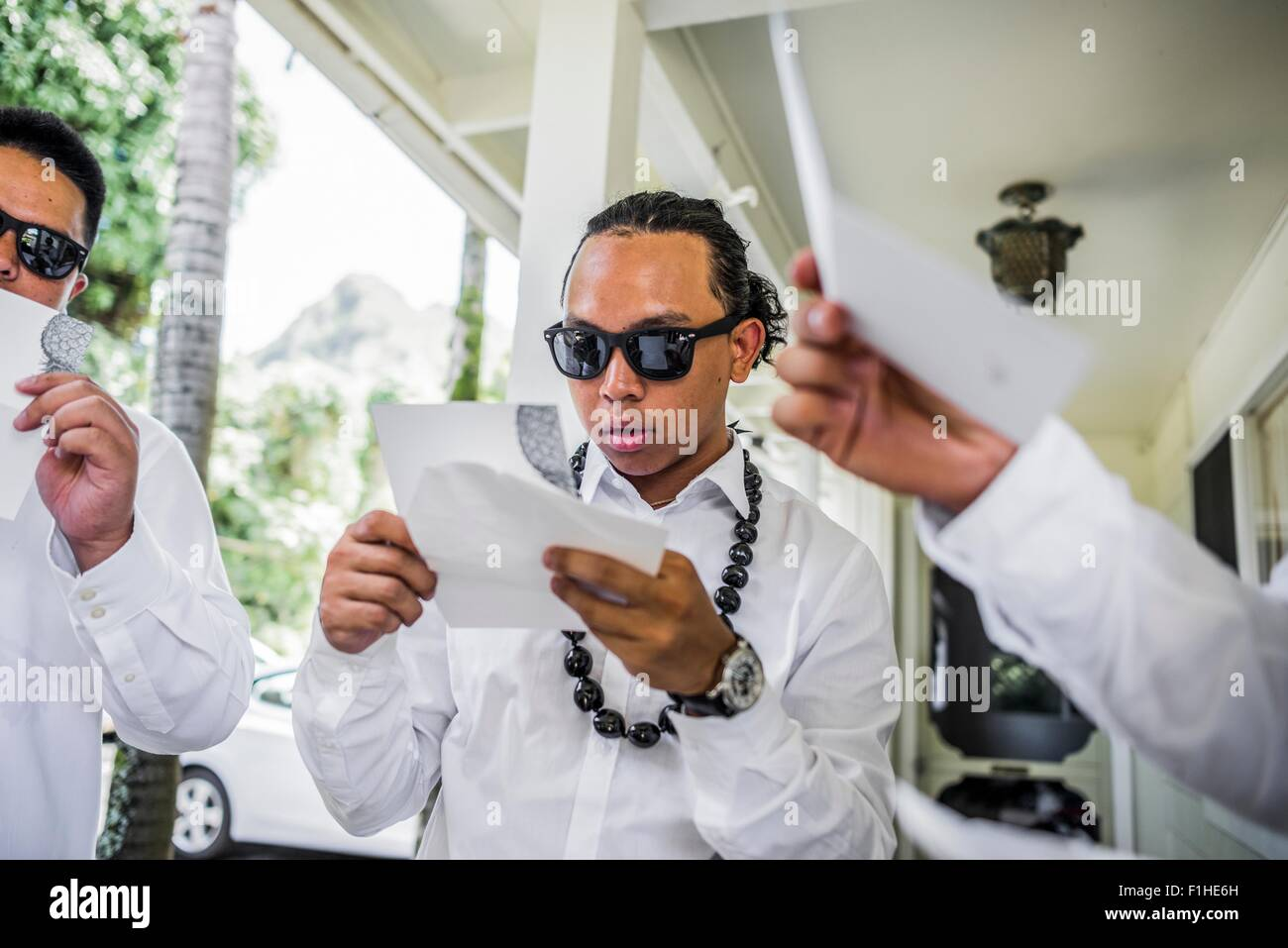 Young men preparing for Hawaiian wedding wearing kukui nut beads, Kaaawa, Oahu, Hawaii, USA - Stock Image