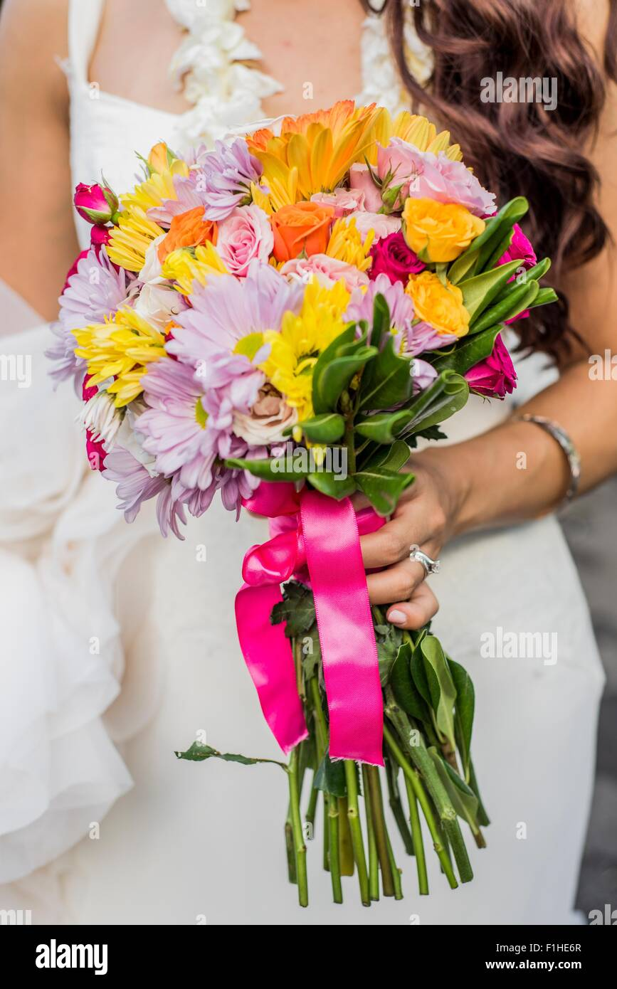 Cropped view of bride and colorful boquet at Hawaiian wedding, Kaaawa, Oahu, Hawaii, USA - Stock Image