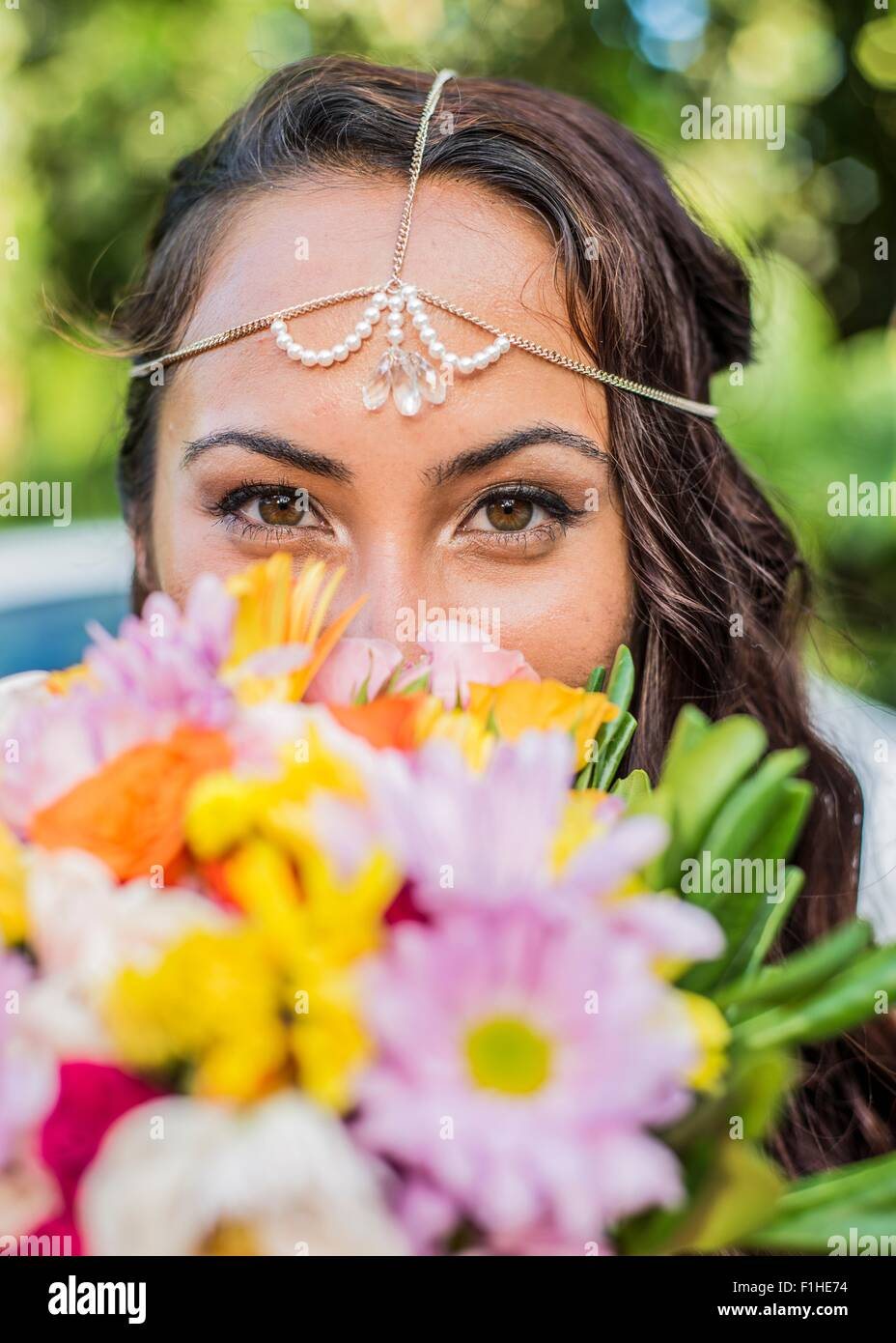 Close up portrait of bride behind colorful boquet at Hawaiian wedding, Kaaawa, Oahu, Hawaii, USA - Stock Image