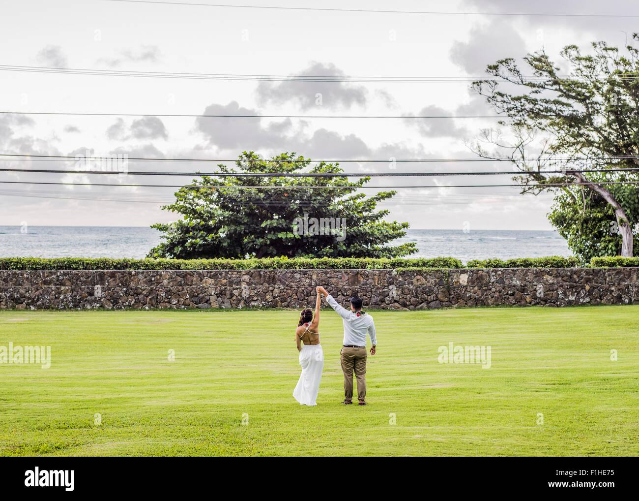 Rear view of bride and bridegroom holding raised hands in garden at Hawaiian wedding, Kaaawa, Oahu, Hawaii, USA - Stock Image