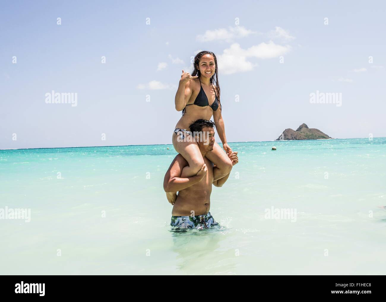 Portrait of young woman getting shoulder ride from boyfriend in sea at Lanikai Beach, Oahu, Hawaii, USA - Stock Image