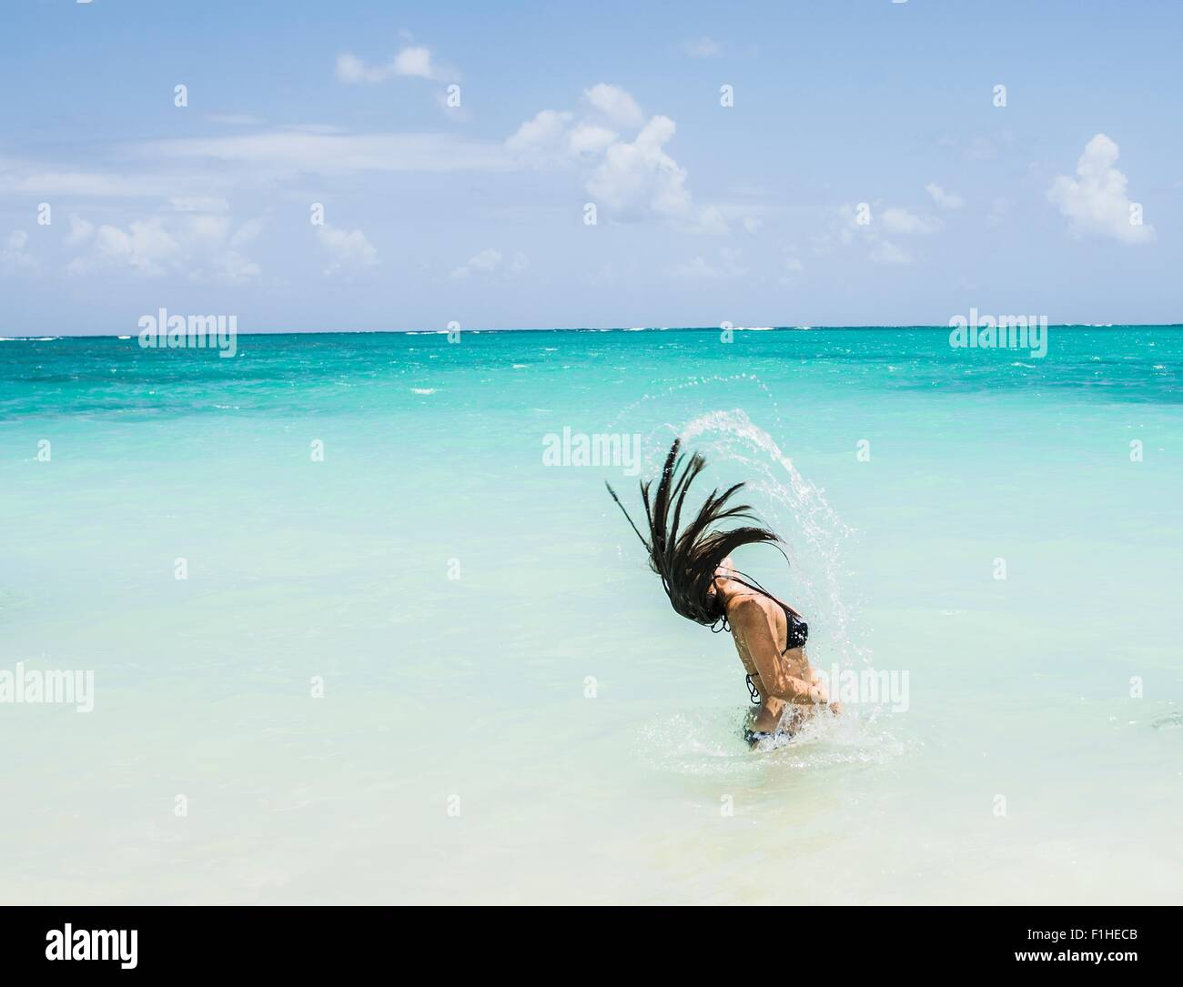 Side view of young woman throwing long wet hair back in sea at Lanikai Beach, Oahu, Hawaii, USA - Stock Image