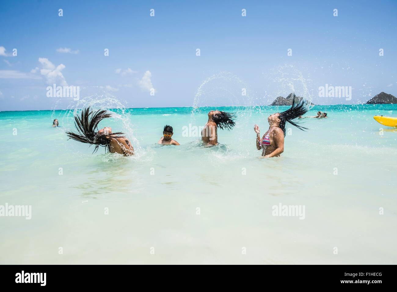 Side view of young women throwing long wet hair back in sea at Lanikai Beach, Oahu, Hawaii, USA - Stock Image