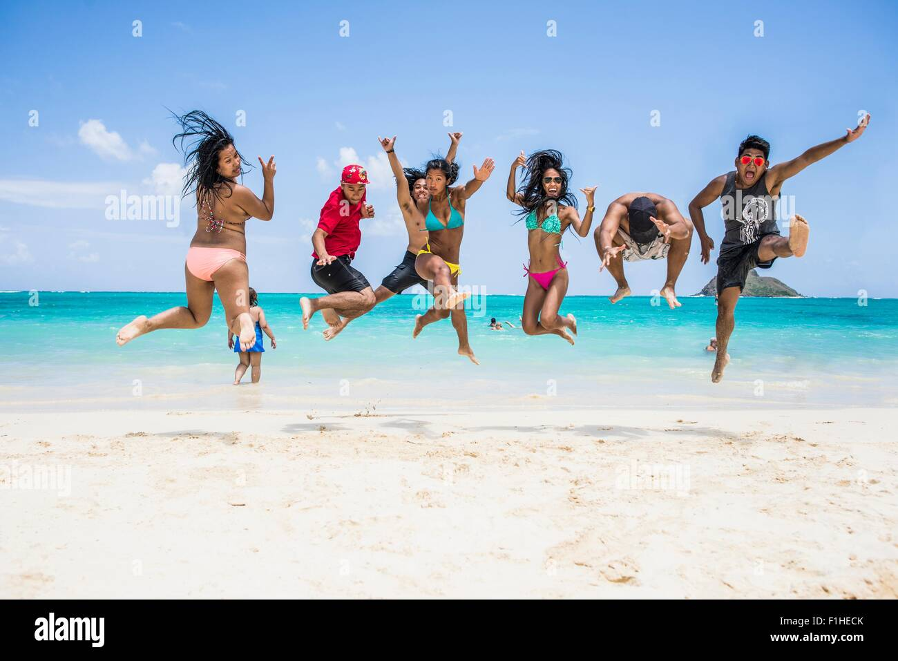 Seven young adults jumping mid air on Lanikai Beach, Oahu, Hawaii, USA - Stock Image