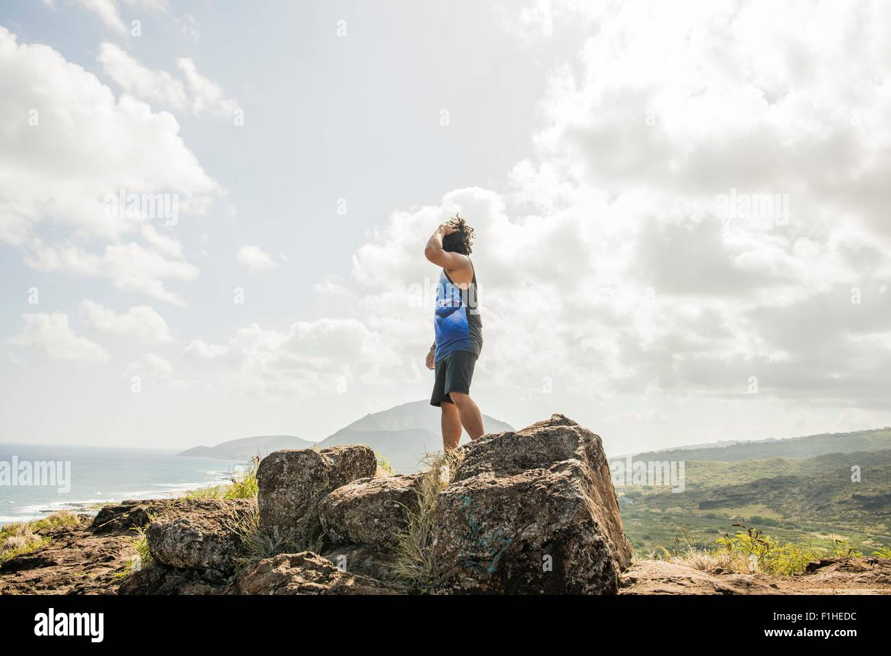Young man looking out from Makapuu coast path, Oahu, Hawaii, USA - Stock Image