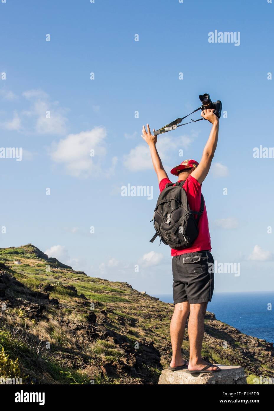 Young male tourist holding up his digital SLR on Makapuu coast path, Oahu, Hawaii, USA - Stock Image
