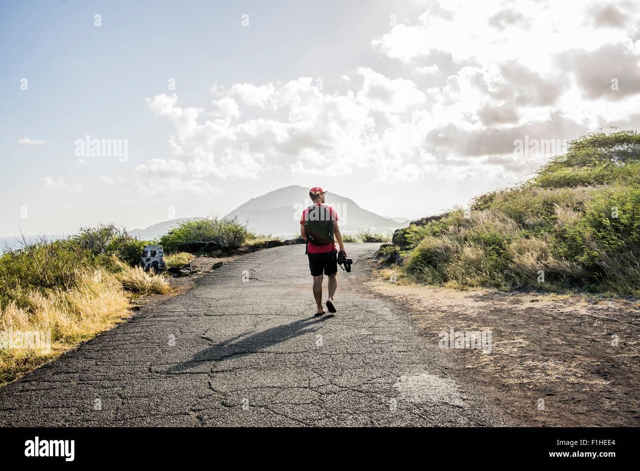 Young male tourist strolling with digital SLR on Makapuu coast path, Oahu, Hawaii, USA - Stock Image