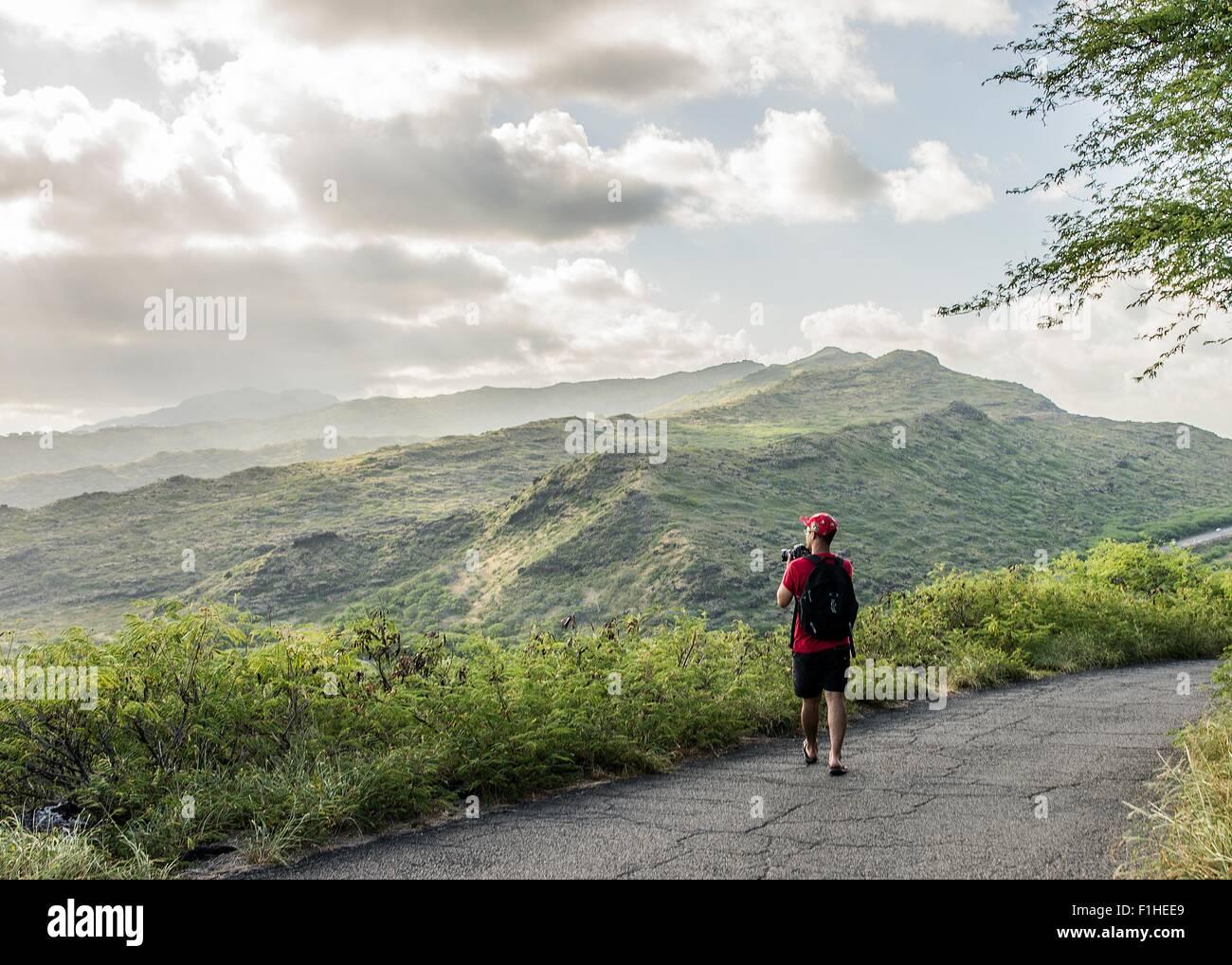 Young male tourist photographing with digital SLR on Makapuu coast path, Oahu, Hawaii, USA - Stock Image