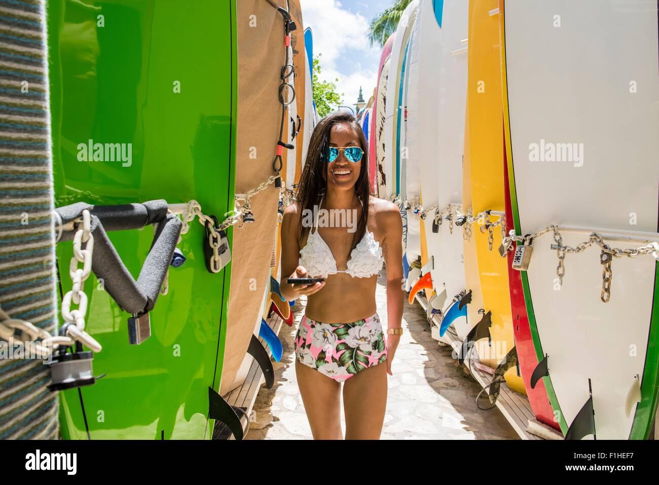 Portrait of young woman standing between surfboards wearing bikini , Waikiki beach, Oahu, Hawaii, USA - Stock Image