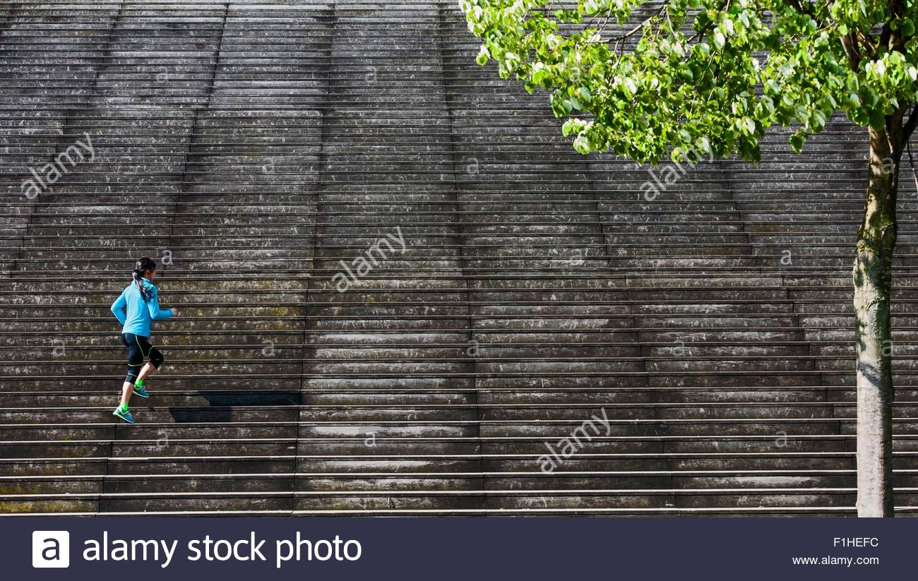 Distant view of female runner running diagonally up wooden stairway - Stock Image