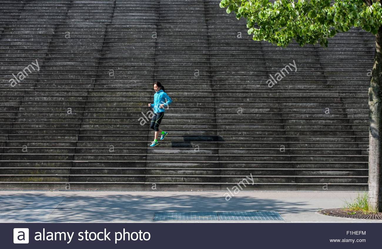 Distant view of female runner running diagonally down wooden stairway - Stock Image