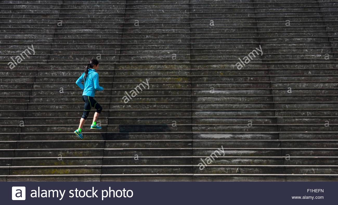 Mature female runner running diagonally up wooden stairway - Stock Image