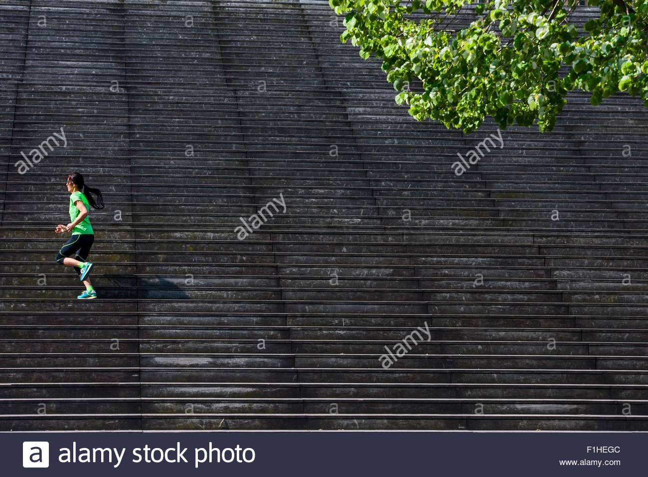 Female runner running diagonally up wooden stairway - Stock Image