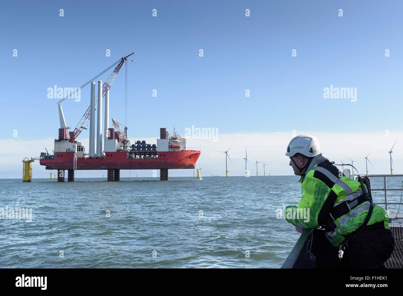 Worker looking at construction ship and offshore windfarm - Stock Image