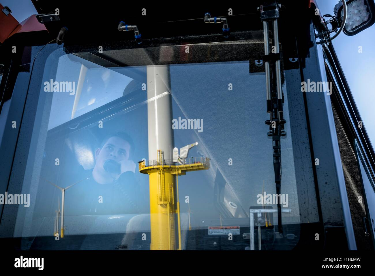 Captain of boat speaking on radio in bridge on offshore wind farm - Stock Image