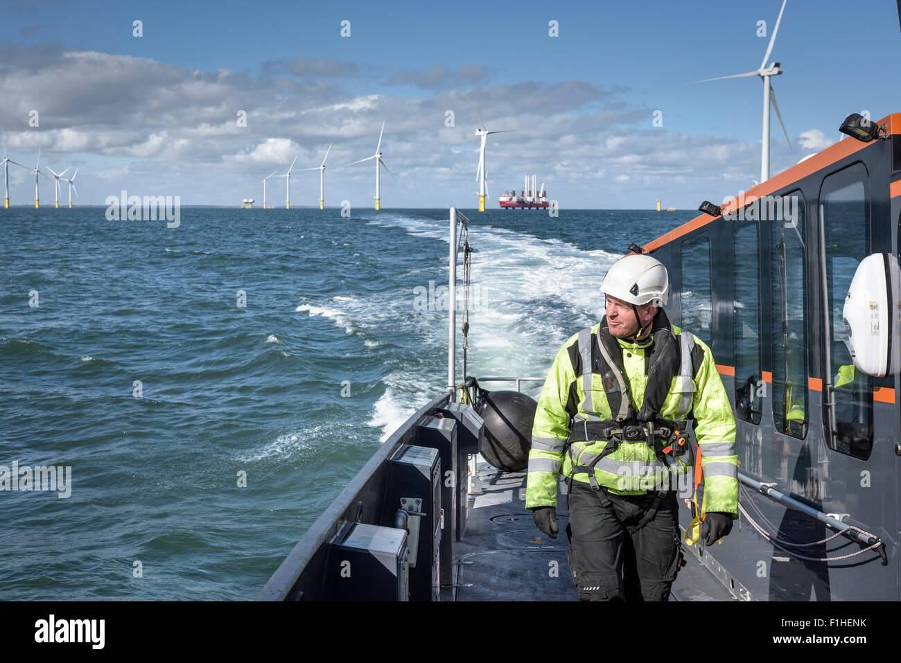 Crew member on deck of boat on offshore wind farm Stock Photo