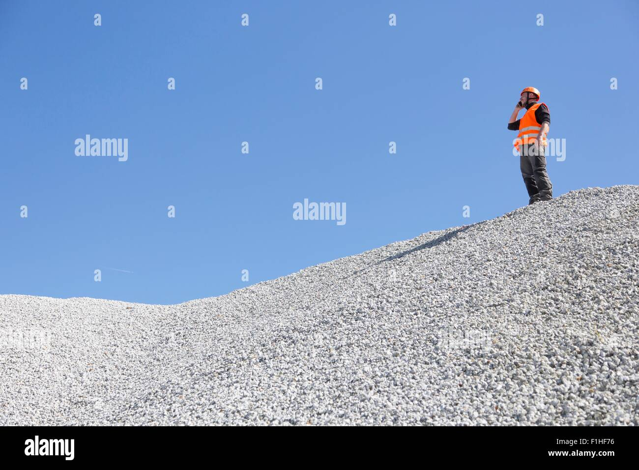 Quarry worker chatting on smartphone from quarry gravel mound - Stock Image