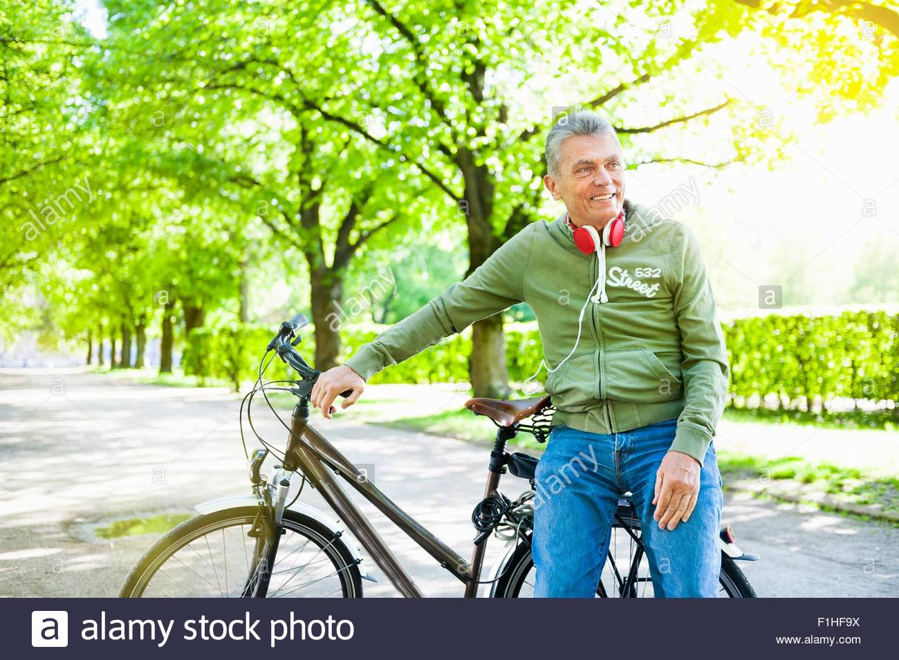 Senior man leaning against bicycle, looking away - Stock Image
