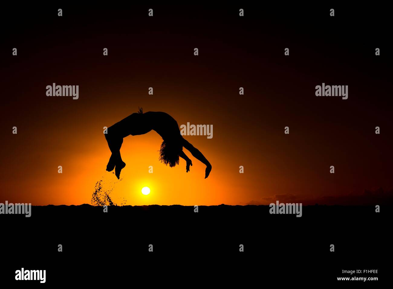 Silhouette of man doing back flip, at sunset, Omakaha, Oahu, Hawaii - Stock Image