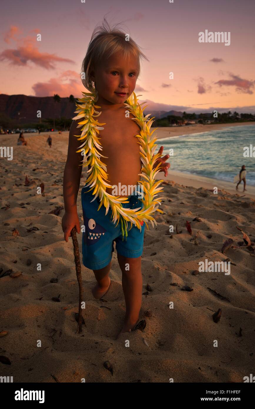Young boy, wearing hawaiian garland, walking along beach, Makaha, Oahu Island, Hawaii - Stock Image