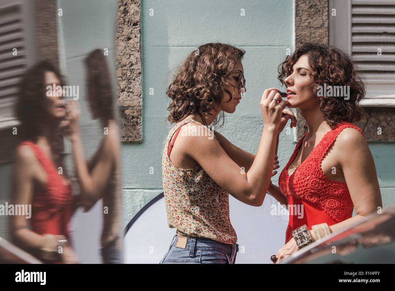 Behind the scenes of an urban fashion shoot with make up artist applying lipstick to model - Stock Image