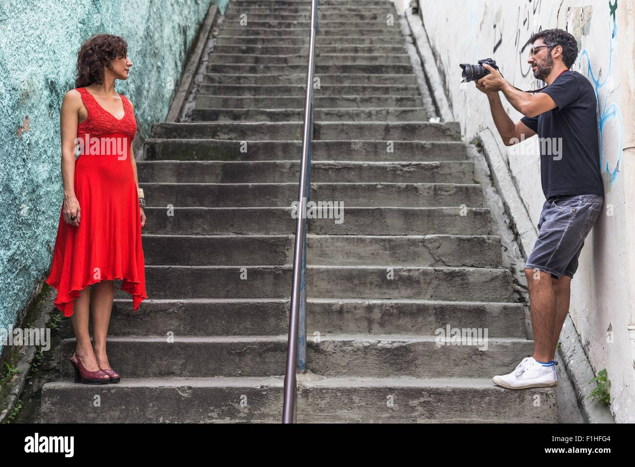 Behind the scenes of an urban fashion shoot with female model and male photographer - Stock Image