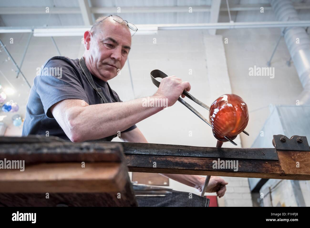 Glassblower forming molten glass - Stock Image