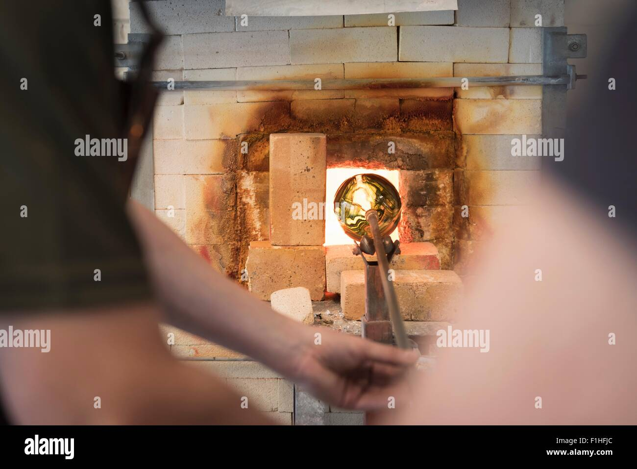 Glassblower heating formed glass in furnace - Stock Image