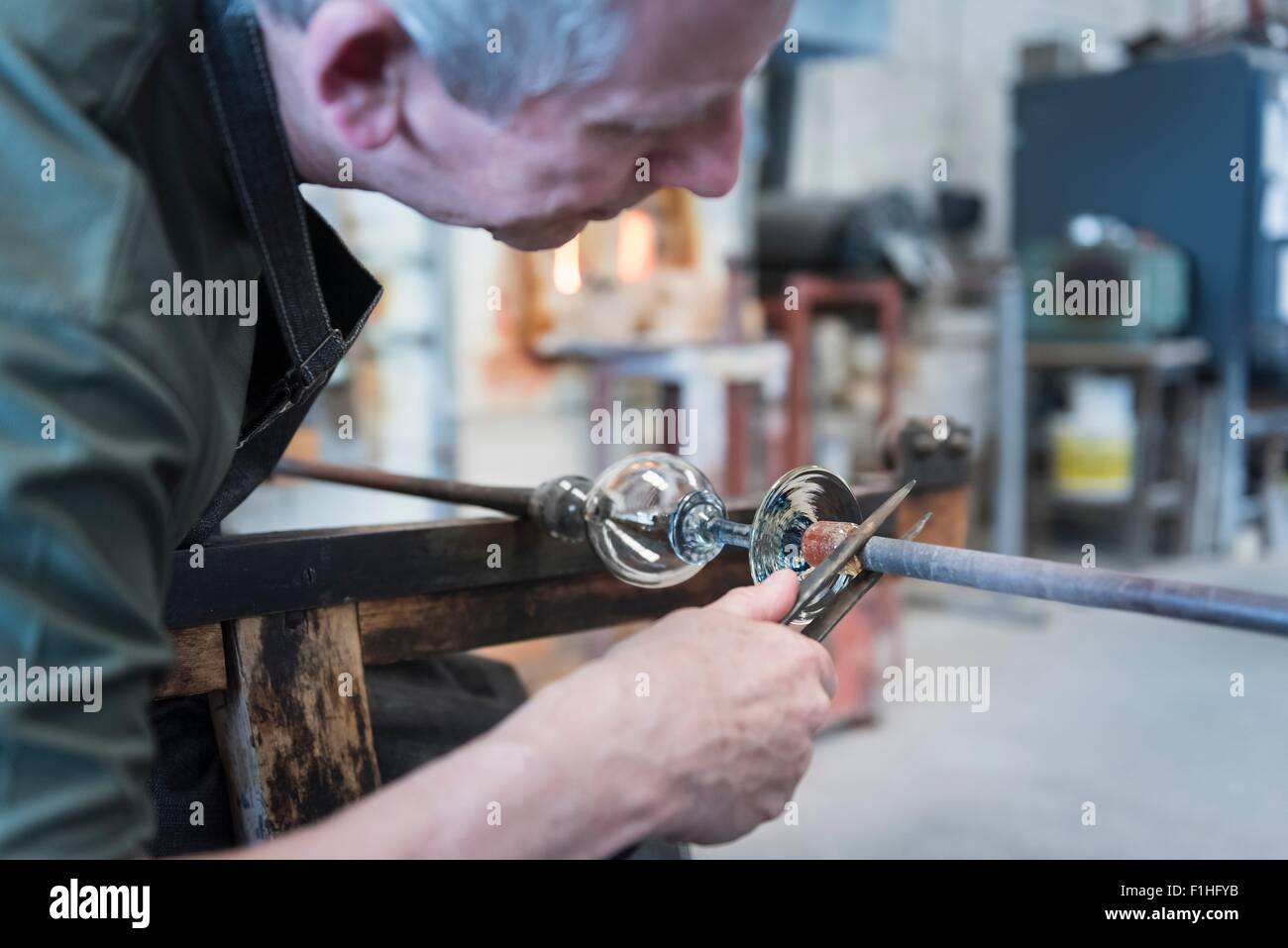 Glassblower forming hot glass object - Stock Image