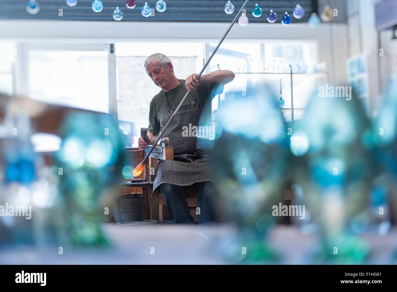 Glassblower with large blob of hot glass - Stock Image