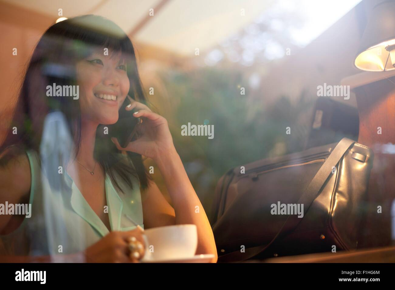 Young woman drinking coffee in cafe, using smartphone, Shanghai, China - Stock Image
