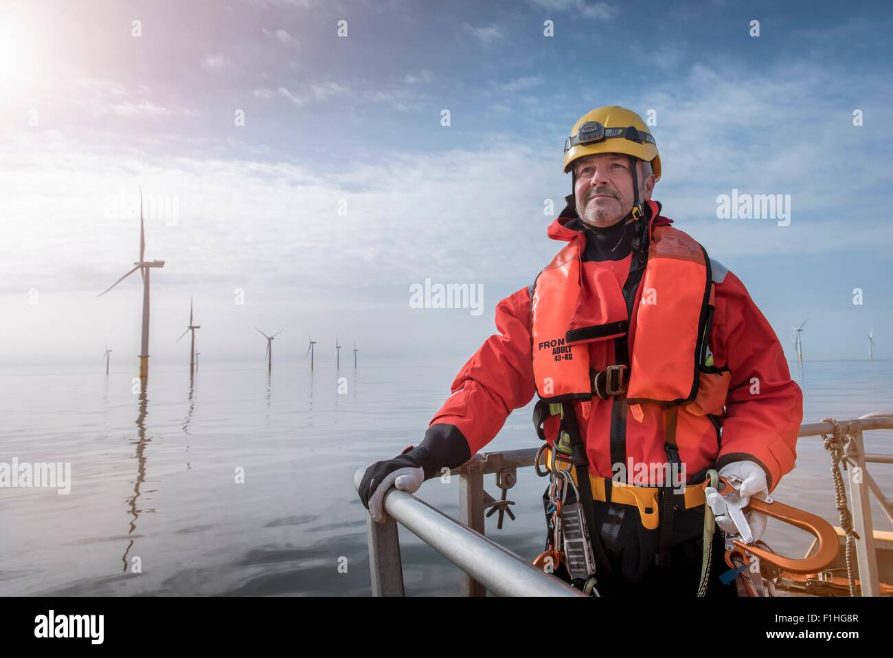 Portrait of engineer on boat at offshore windfarm - Stock Image