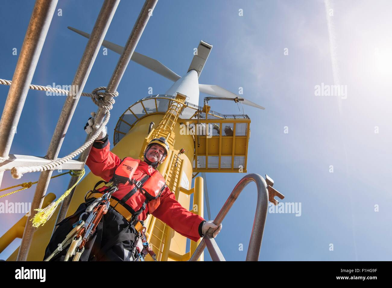 Engineer preparing to climb windturbine at offshore windfarm, low angle view - Stock Image