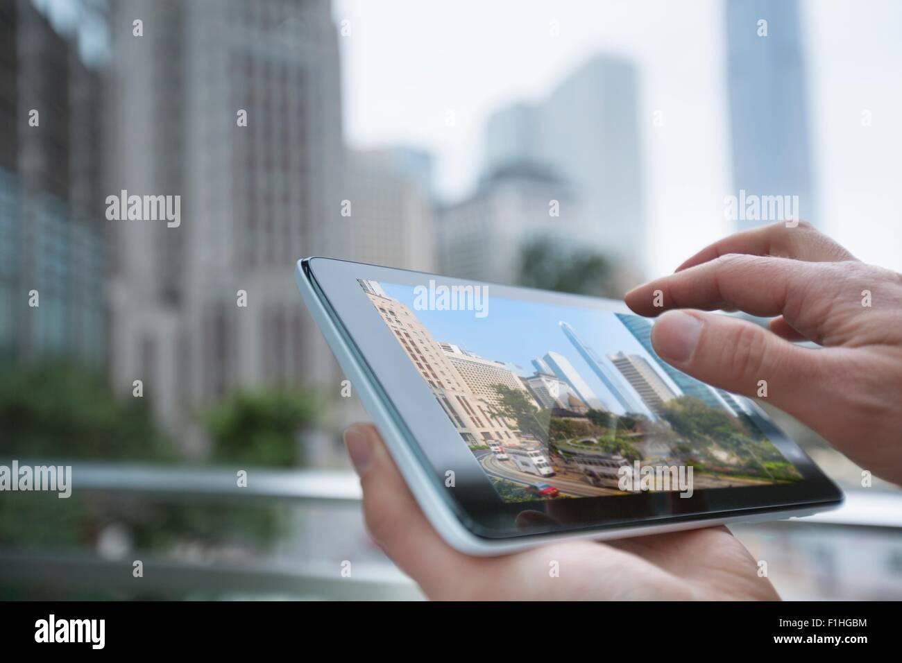 Man using digital tablet, focus on hands, Hong Kong, China - Stock Image