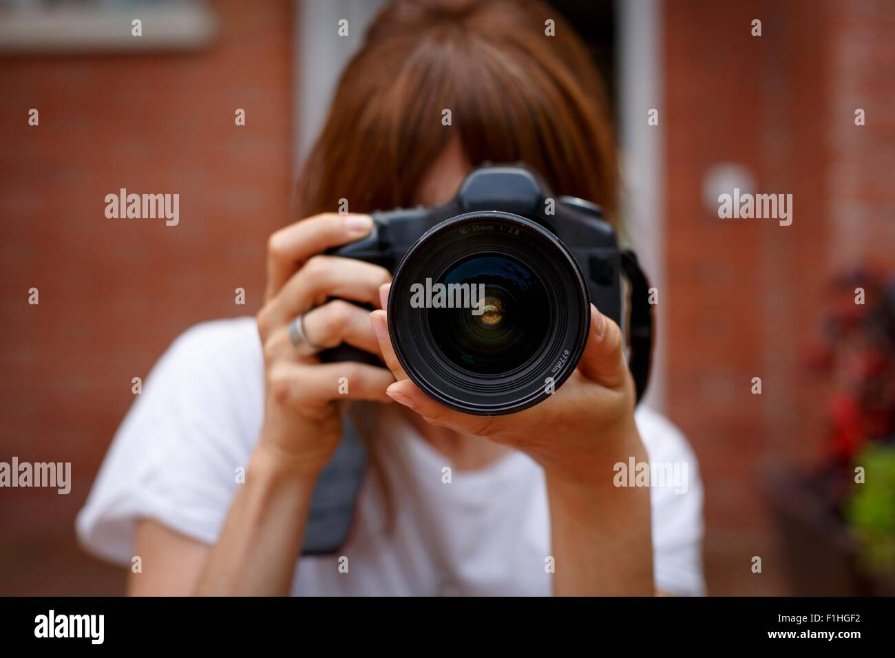 Mid adult woman using digital camera, face obscured - Stock Image