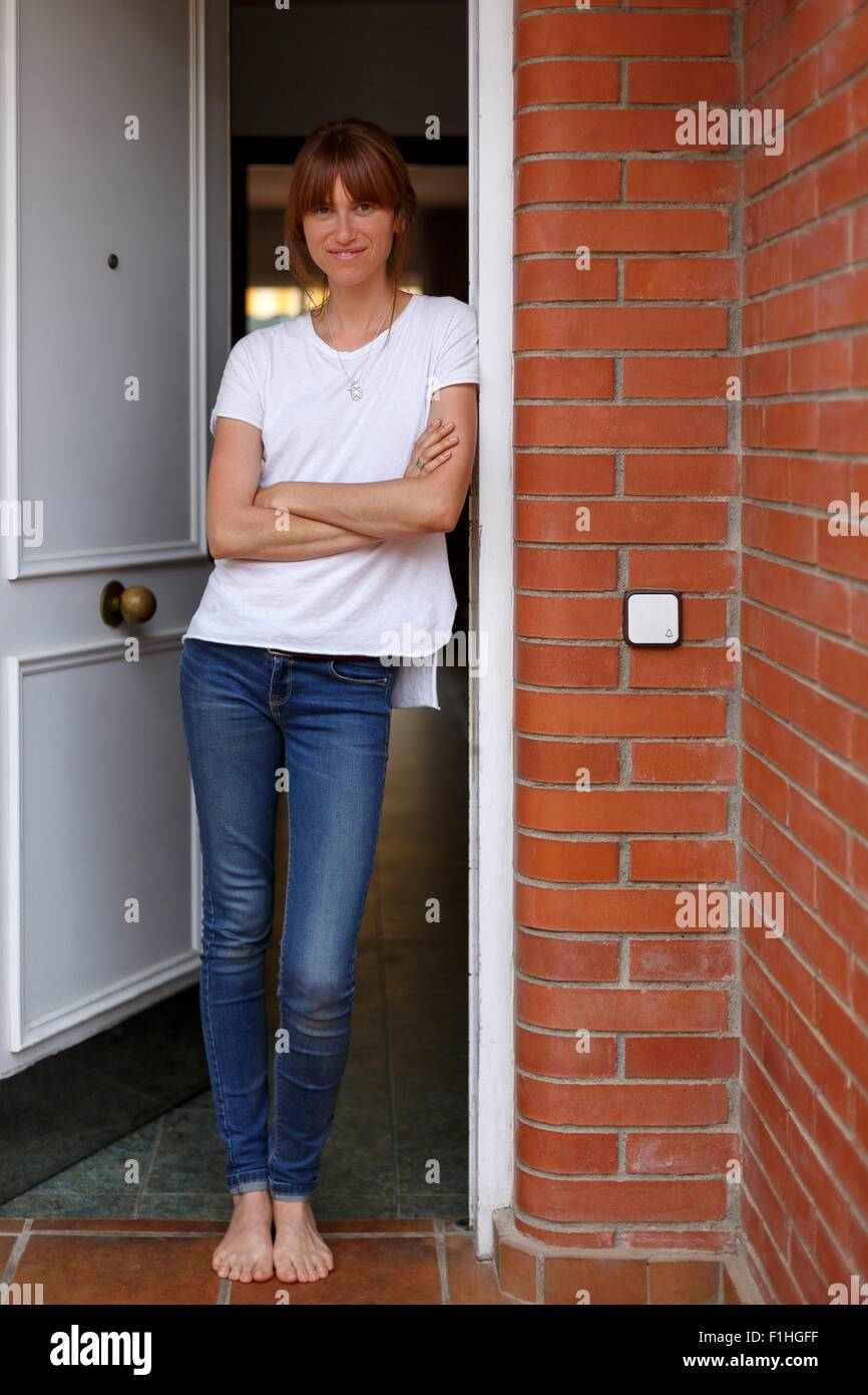 Full length view of mid adult woman leaning against door frame, arms crossed - Stock Image