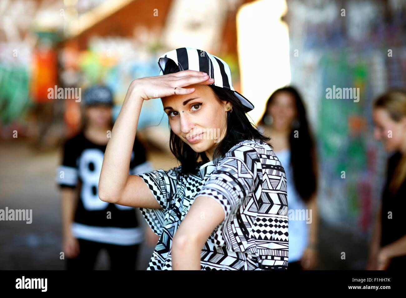 Young woman wearing baseball cap backwards, looking at camera - Stock Image