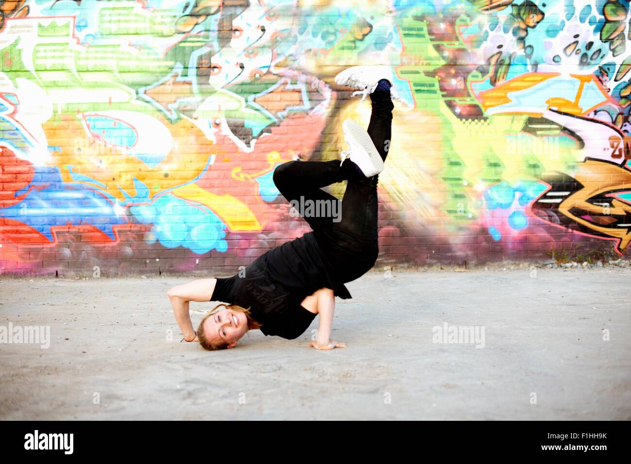 Young woman in upside down breakdancing freeze against graffiti Stock Photo