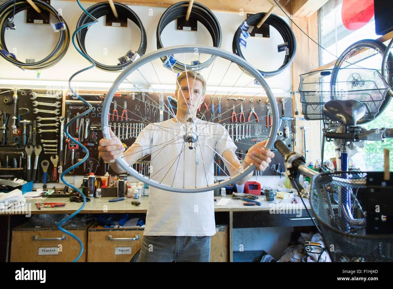 Mid adult man in repair shop looking through bicycle wheel Stock Photo