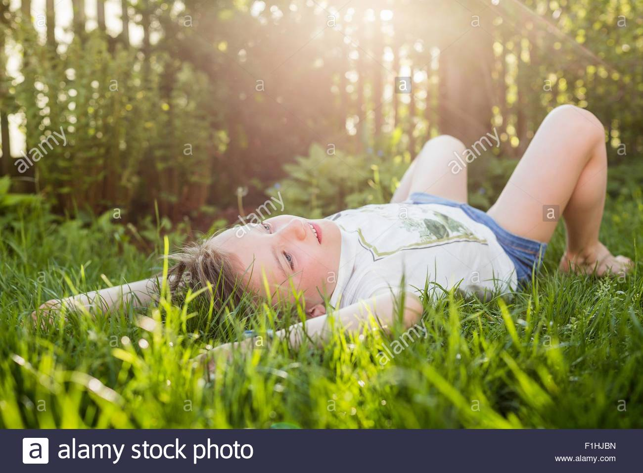 Girl lying on grass gazing in garden - Stock Image